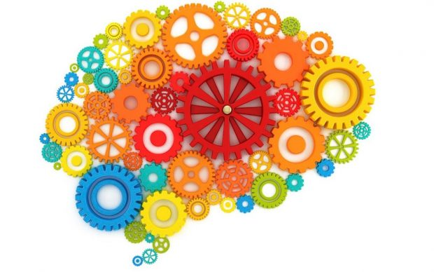 Brightly coloured, differently sized cogs forming the shape of a brain.