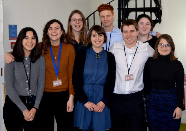 A smiley group photo of eight of the Open Innovation Team's PhD students. From left to right: Sarah Oufan, Rosa Hodgkin, Sophia Peacock, Lizzie Atkinson, Marc Goldfinger, Peter West, Sarah Sheehy, and Rachel Efrat.