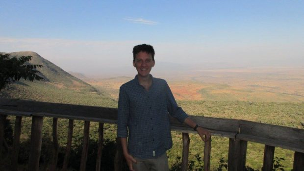 Image shows Matt Tyce, a PhD student secondee at the Open Innovation Team, with a view of the Rift Valley in Kenya behind him.