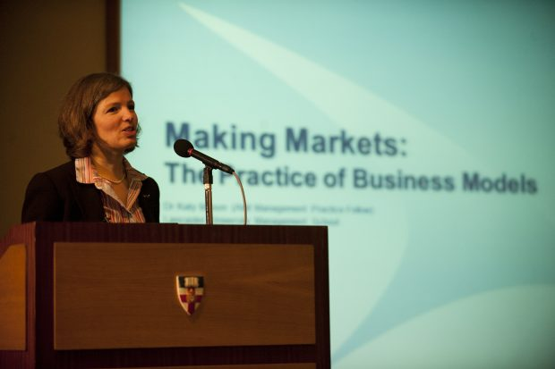 The image shows Katy Mason, the author of this blog post, giving a talk with her presentation behind her which reads 'Making Markets: The Practise of Business Models'