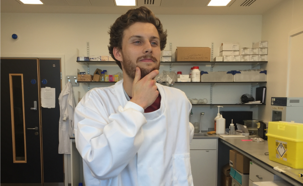 PhD placement student Michael Norman posing for the camera in the laboratory in his white lab coat.